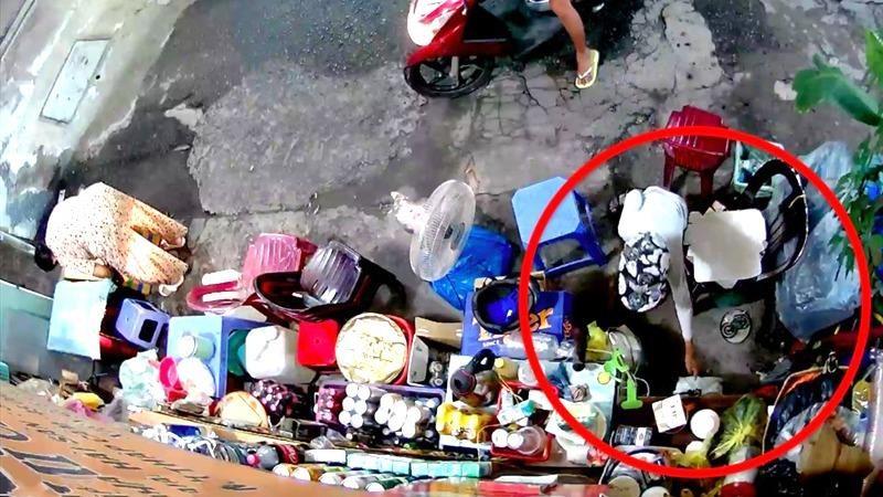 Đứa trẻ trộm tiền của bà bán nước khi mẹ nuôi đang ngồi trên xe chờ sẵn.