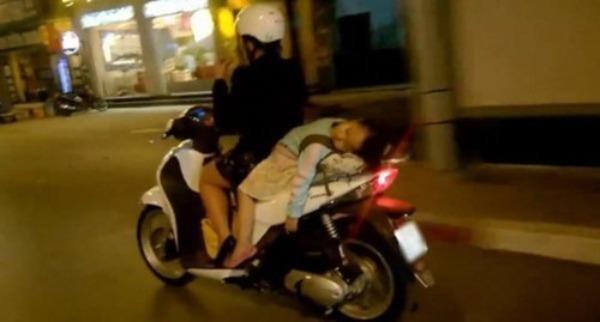 Người mẹ cho con đang ngủ di chuyển trên đường.