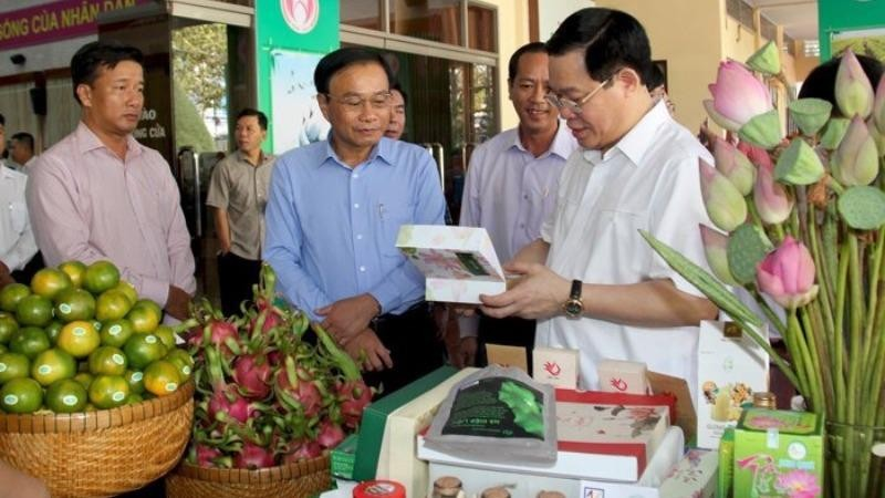 Chủ tịch UBND tỉnh Đồng Tháp Nguyễn Văn Dương giới thiệu các sản phẩm của tỉnh với đồng chí Vương Đình Huệ - Ủy viên Bộ Chính trị, Bí thư Thành uỷ Hà Nội (lúc đó là Phó Thủ tướng Chính phủ).