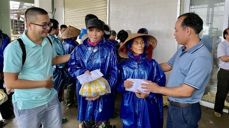 Nhà báo Nguyễn Quang Tám - Trưởng Văn phòng Báo PLVN khu vực Bình Trị Thiên (ngoài cùng bên phải) trao quà cho người dân vùng lũ.