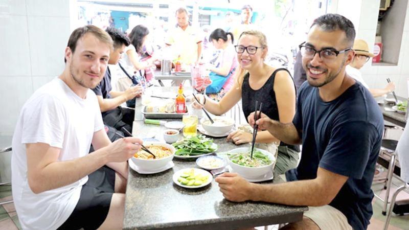Du khách nước ngoài thưởng thức ẩm thực Việt.
