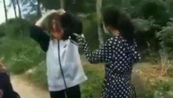 Hình ảnh nữ sinh dùng mũ bảo hiểm đánh bạn. Hình ảnh cắt từ clip.