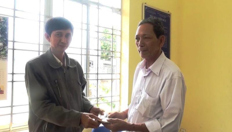 Ông Nguyễn Văn Thái (bên trái) trao lại số tài sản nhặt được cho người đánh rơi tại trụ sở Công an xã.