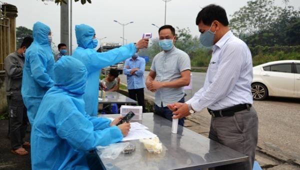 Lực lượng chức năng tại chốt kiểm soát đo thân nhiệt và hướng dẫn người dân rửa tay sát khuẩn.