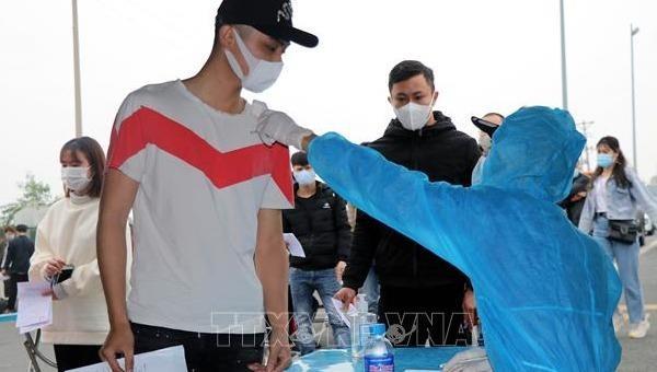 Những người rời Quảng Ninh thực hiện đo thân nhiệt tại trạm kiểm soát dịch bệnh COVID-19 cầu Bạch Đằng (huyện Quảng Yên). Ảnh: TTXVN.