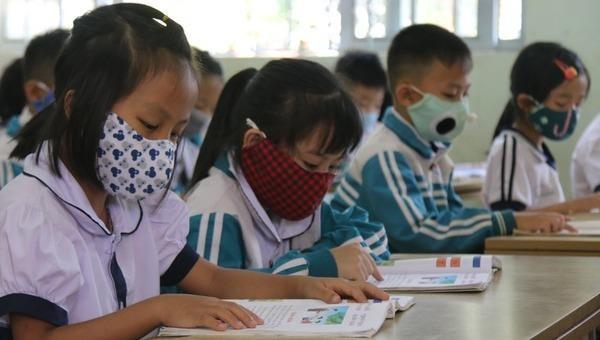 Học sinh Đắk Nông đeo khẩu trang, được kiểm tra thân nhiệt trước khi vào lớp. Ảnh Dân trí