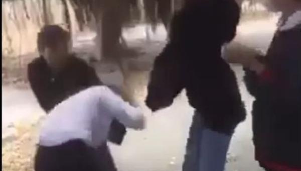Một em mang áo khoác đen dùng mũ bảo hiểm đánh vào vùng đầu nữ sinh.