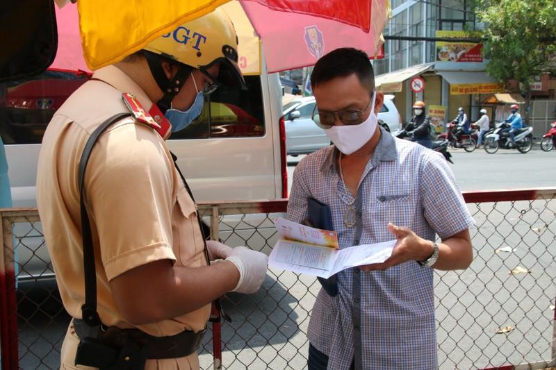 Sau khi được đo thân nhiệt các tài xế xuất trình giấy tờ để CSGT kiểm tra theo quy định.