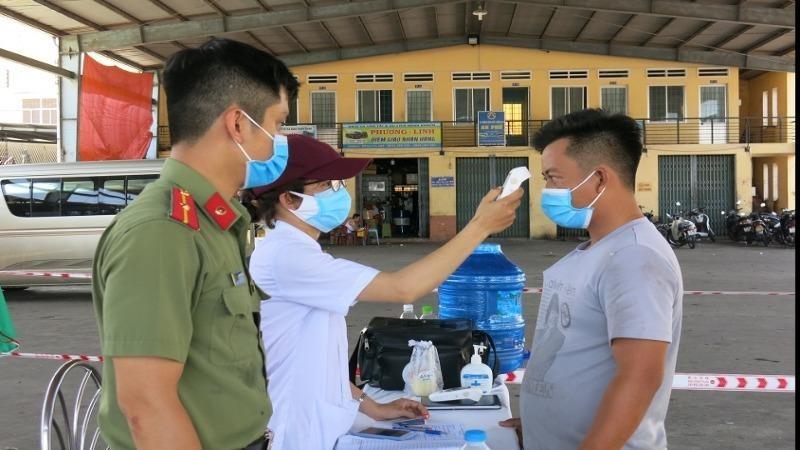 Nhân viên y tế Bình Định kiểm tra thân nhiệt hành khách tại Bến xe khách trung tâm Quy Nhơn. Ảnh: Thu Phương