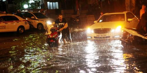 Người dân ở Hà Nội lại phải bì bõm trong nước ngập sâu sau cơn mưa chiều tối ngày 26/8.