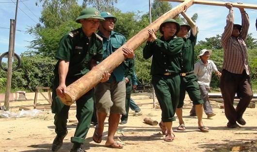Cán bộ, chiến sĩ Bộ đội Biên phòng lao động giúp nhân dân sửa chữa cầu đường.