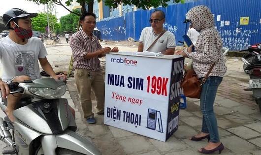 Mua sim tặng điện thoại bày bán vỉa hè trên các tuyến đường ở Hà Nội.