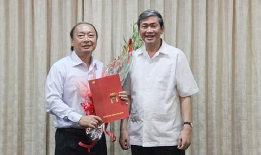 Đồng chí Đinh Thế Huynh (phải) trao quyết định và tặng hoa chúc mừng đồng chí Võ Văn Phuông