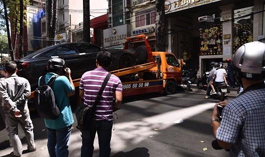 Một chiếc ô tô để xe dưới lòng đường bị cơ quan chức năng cẩu đi.