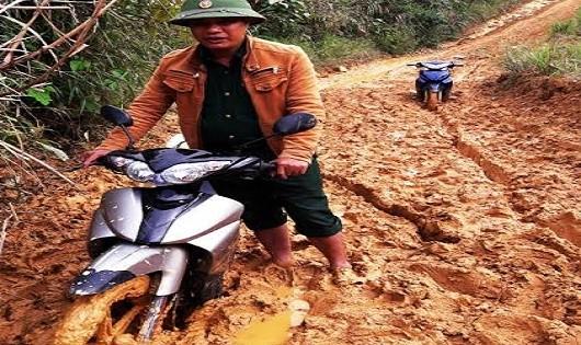 Thiếu tá Lê Văn Thắng dắt xe qua bùn lầy.