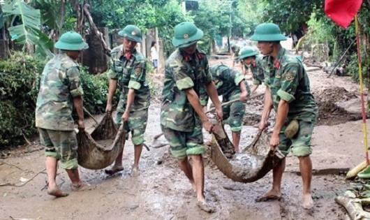Bộ đội giúp dân khắc phục hậu quả sau bão lũ.