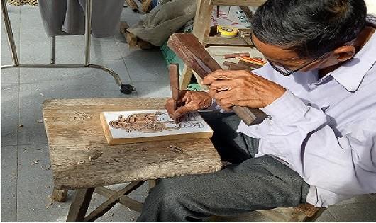 Nghệ nhân Kỳ Hữu Phước đang say sưa khắc bản gỗ, đảm bảo số lượng sản phẩm phục vụ Tết Nguyên đán cho bà con, du khách gần xa.