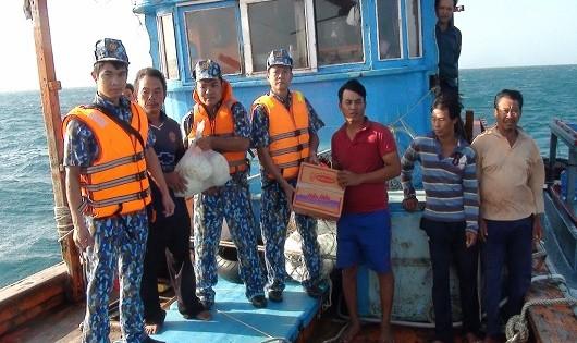 Cán bộ, chiến sĩ tàu CSB 9001 tặng lương thực, thực phẩm cho các ngư dân tàu KH 99036TS sau khi cứu nạn tàu cá ngày 12/3/2018