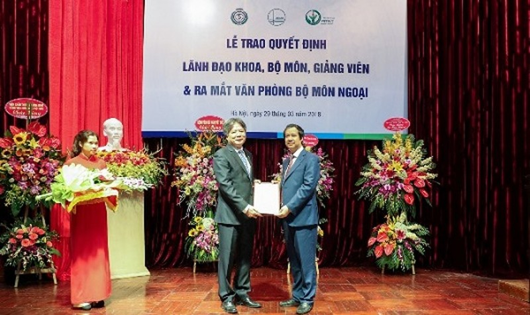 Giám đốc ĐHQGHN Nguyễn Kim Sơn (bên phải) trao Quyết định bổ nhiệm lại cho GS.TS Trần Bình Giang.