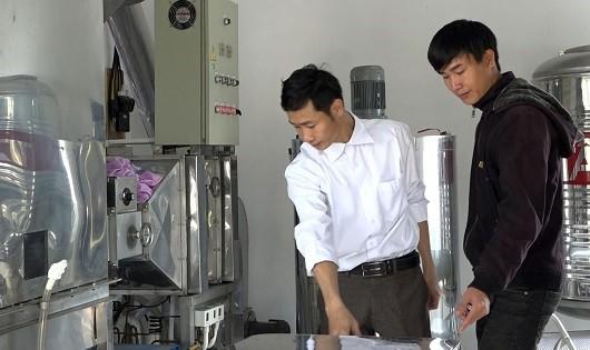 Anh Nguyễn Văn Hưởng (trái) giới thiệu về máy hạ thủy phần mật ong.