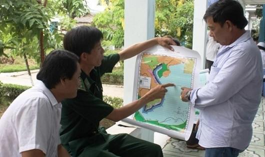 Cán bộ Đồn Biên phòng Sông Đốc phát tờ rơi tuyên truyền, vận động ngư dân không vi phạm các quy định hoạt động nghề cá.