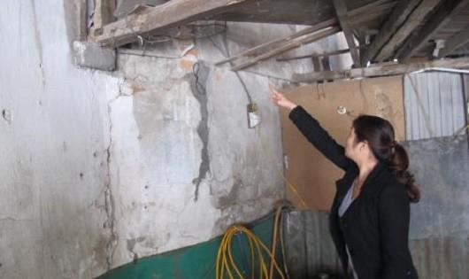 Bà Lập (vợ ông Thủy) chỉ bức tường đã sập trước đó. Ảnh TTXVN