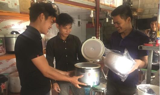 Anh Nông Văn Dũng đang tư vấn cho khách hàng trong cơ sở sản xuất kinh doanh được tạo lập từ nguồn vốn chính sách.