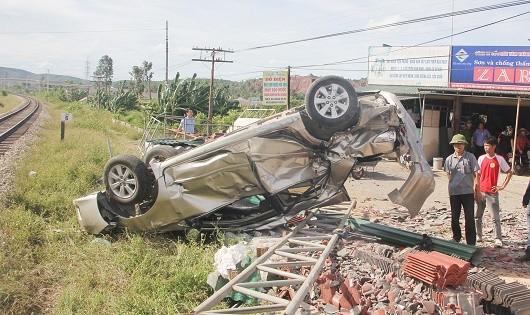 Xe ô tô bị tàu hỏa hất văng nằm phơi bụng khi cố vượt qua đoạn giao cắt.