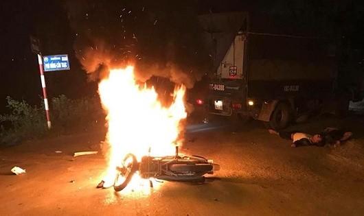 Chiếc xe máy của hai thanh niên bốc cháy dữ dội sau cú va chạm với xe tải.