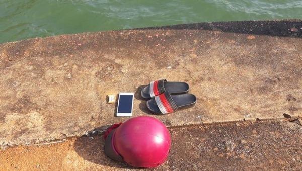 Điện thoại, mũ bảo hiểm và đôi dép của chị N. trên bờ.