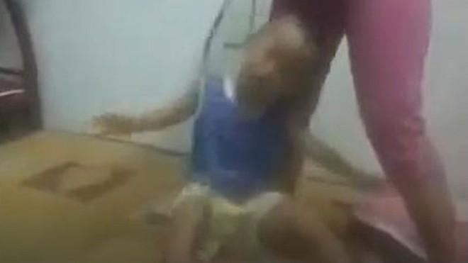 Video ghi lại cảnh một người phụ nữ khoảng 30 tuổi dùng dây thừng buộc vào cổ bé trai khoảng 3 tuổi và dùng vũ lực đánh đập