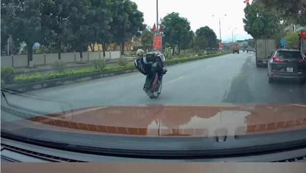 """Nam thanh niên """"bốc đầu"""" xe máy trên quốc lộ 7A được camera hành trình của một ô tô ghi lại (ảnh cắt từ clip)."""