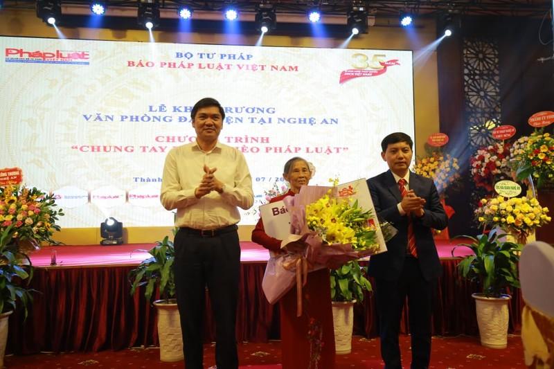 Mẹ Việt Nam anh hùng Nguyễn Thị Lan (ở giữa) nhận hoa và sổ tiết kiệm do Báo Pháp luật Việt Nam trao tặng.