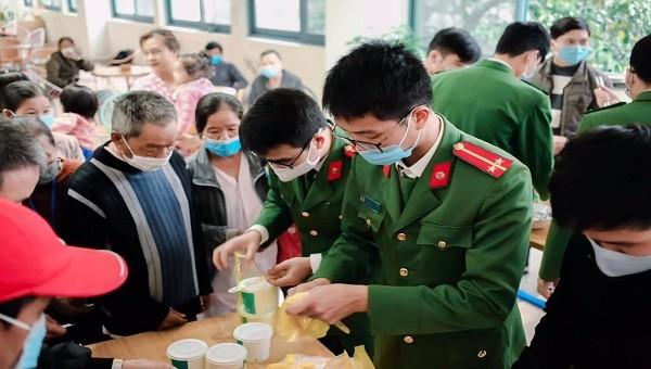 Các chiến sĩ Công an thị xã Hương Trà phát cháo cho các bệnh nhân.