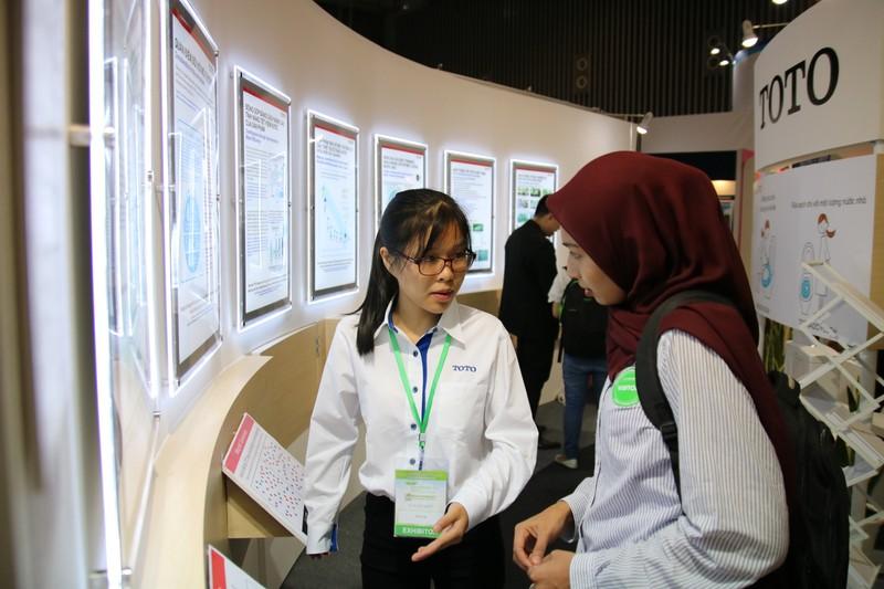 Nhân viên TOTO Việt Nam giới thiệu với khách tham quan gian hàng của Tập đoàn TOTO. Ảnh: MINH QUỐC