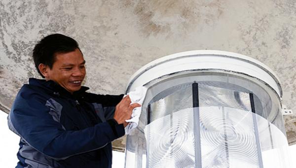 Trạm trưởng Trạm Hải đăng Vĩnh Thực Vũ Văn Dụng đang bảo dưỡng đèn biển để đảm bảo chiếu sáng phục vụ an toàn Hàng hải