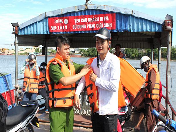 Công an tỉnh Nam Định hướng dẫn hành khách sử dụng áo phao khi tham gia giao thông thủy trên phà Đống Cao.