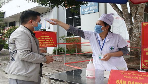 Đo thân nhiệt cho người ra vào Bệnh viện mắt Hà Nam.