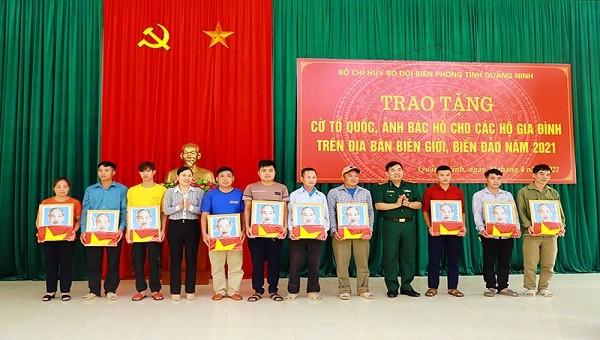 Đại tá Nguyễn Thanh Hải, Chính ủy BĐBP tỉnh Quảng Ninh và Trưởng ban Dân vận Huyện ủy, Chủ tịch MTTQ huyện Bình Liêu trao cờ Tổ quốc và ảnh Bác Hồ cho đại diện các hộ dân.