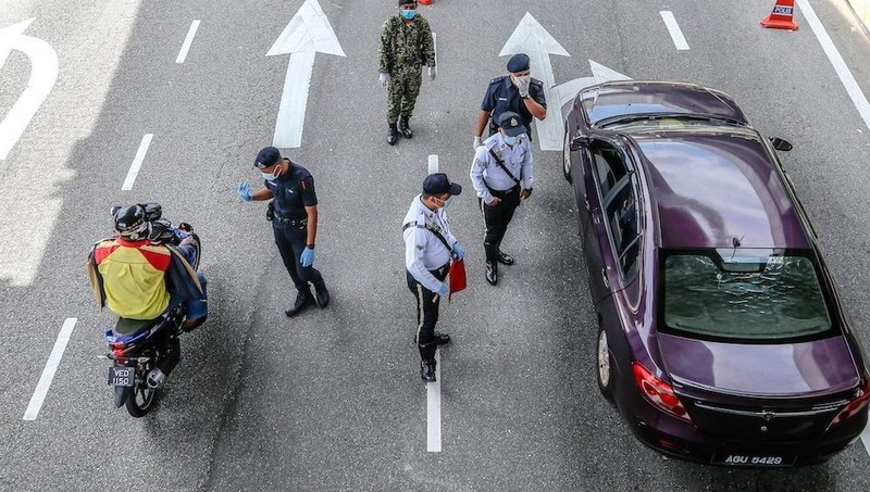 Cảnh sát Malaysia tiến hành kiểm tra người dân vi phạm trên đường phố.