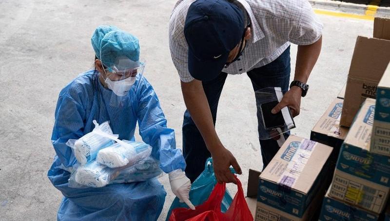Tình nguyện viên phát vật tư y tế cho người lao động nước ngoài tại ký túc xá. Ảnh CNN.