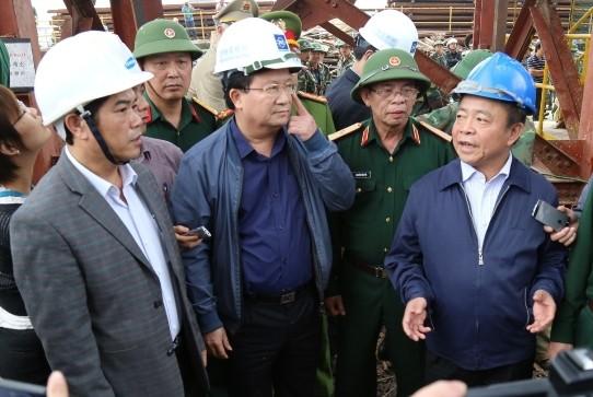 Bộ trưởng Trịnh Đình Dũng (giữa) và Bí thư Tỉnh ủy Võ Kim Cự (phải, mũ xanh) chỉ đọa tại hiện trường.