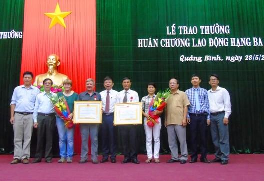 Hồ Khanh và Howard Limbert chụp ảnh lưu niệm cùng lãnh đạo tỉnh Quảng Bình và người thân tại lễ trao tặng huân chương.