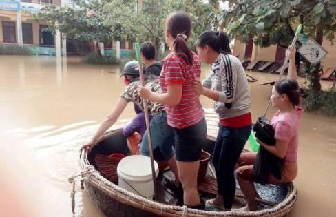 Cán bộ giáo viên Trường Tiểu học số 2 Quảng Văn, thị xã Ba Đồn chèo thuyền thúng vượt lũ vào dọn dẹp trường lớp để học sinh sớm được đến trường. Ảnh: Phương Nhạn