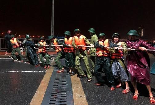 Lực lượng biên phòng dùng dây thừng kéo tàu về lại neo đậu an toàn.