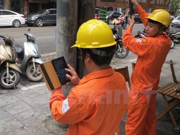 Nhân viên ngành điện ghi chỉ số côngtơ của khách hàng. Ảnh: Vietnam+