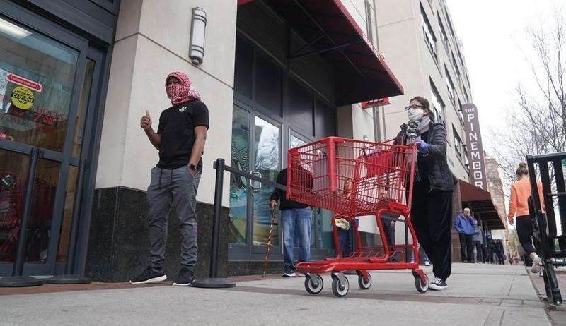 Người dân thực hiện đeo khẩu trang, xếp hàng bên ngoài siêu thị ở Arlington, Virginia ngày 4/4/2020. Ảnh: Xinhua