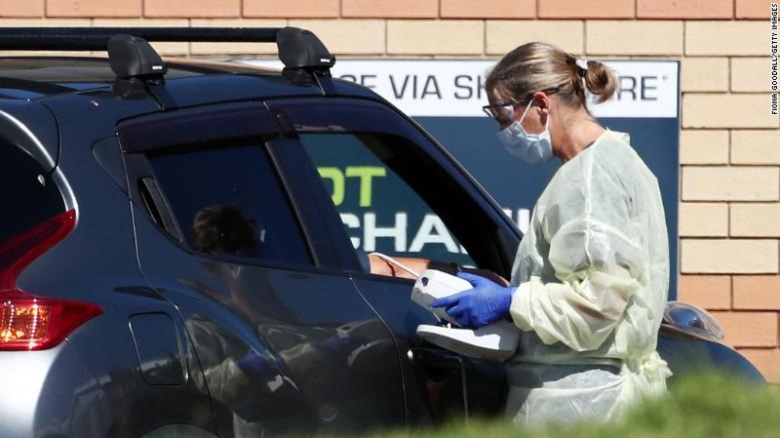 Y tá kiểm tra thân nhiệt người đi đường tại một ổ dịch Covid-19 ở Northcross trên Bờ Bắc tại Auckland, New Zealand. Ảnh: CNN