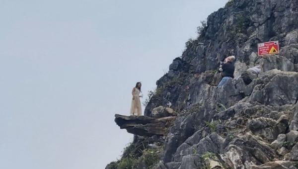 Du khách mạo hiểm chụp ảnh ở mỏm đá tử thần dù có biển cảnh báo nguy hiểm. Ảnh minh họa: Nguyễn Chiến/TTXVN