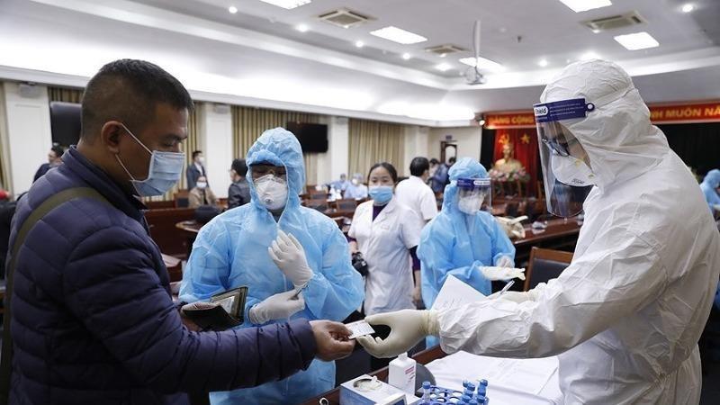 Làm thủ tục lấy mẫu xét nghiệm virus SARS-CoV-2 cho phóng viên tác nghiệp tại Đại hội XIII của Đảng. Ảnh minh họa: Dương Giang/TTXVN